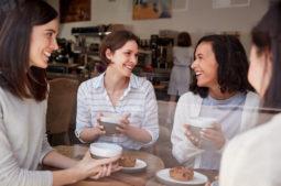 Cuatro chicas jóvenes ríen mientras toman una bebida en una cafetería.